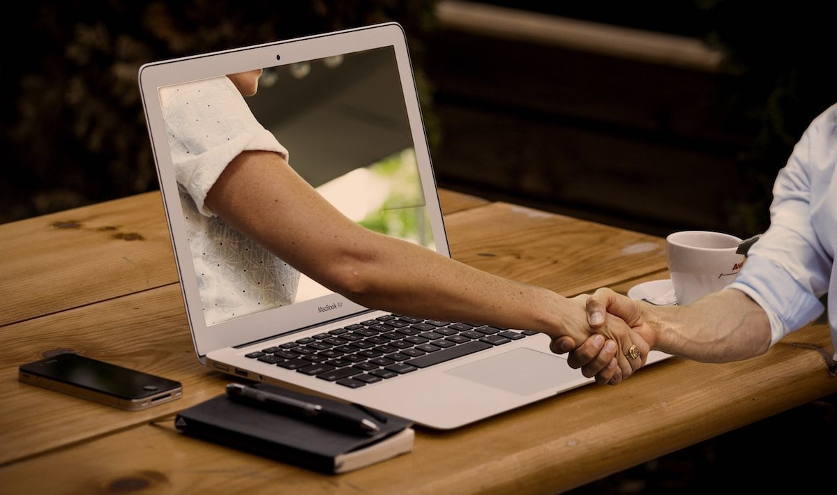 BGM Laptop Handshake zwei Männer Schreibtisch